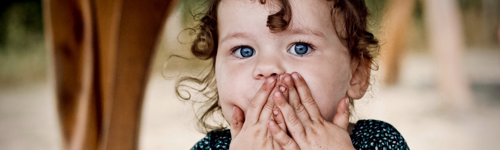 A little girl covering her mouth with her two hands.