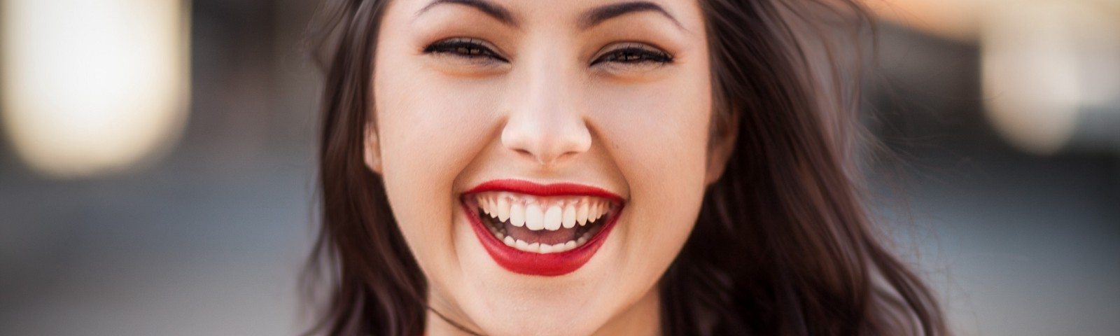 A brown-haired girl with a red sweater and red lipstick smiling.