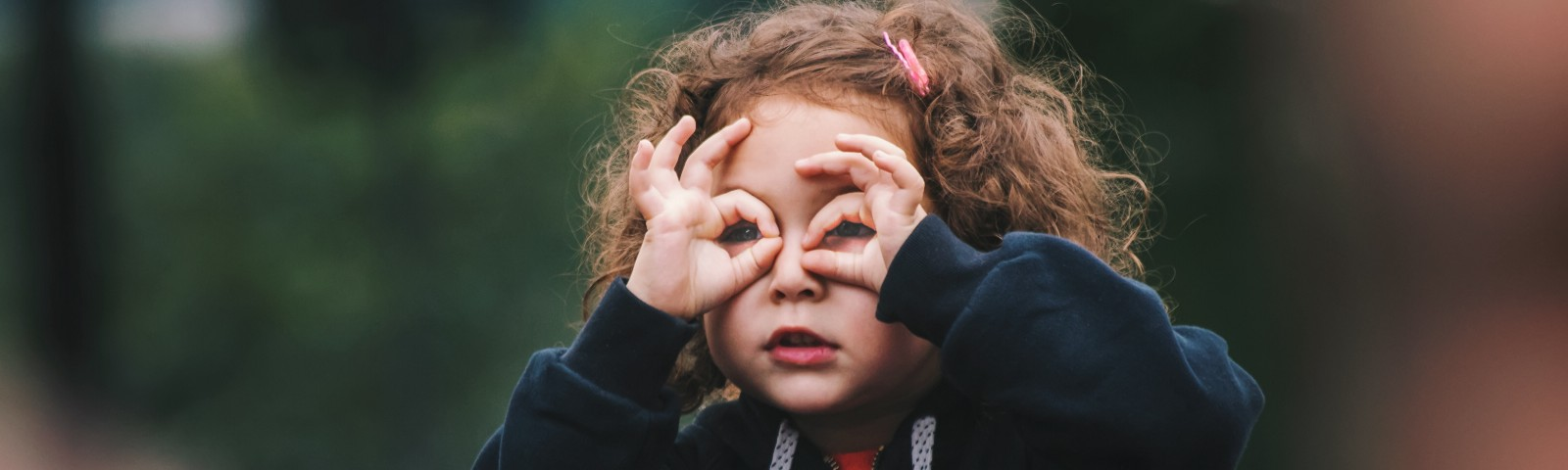 A little girl seeing through the lens of her fingers