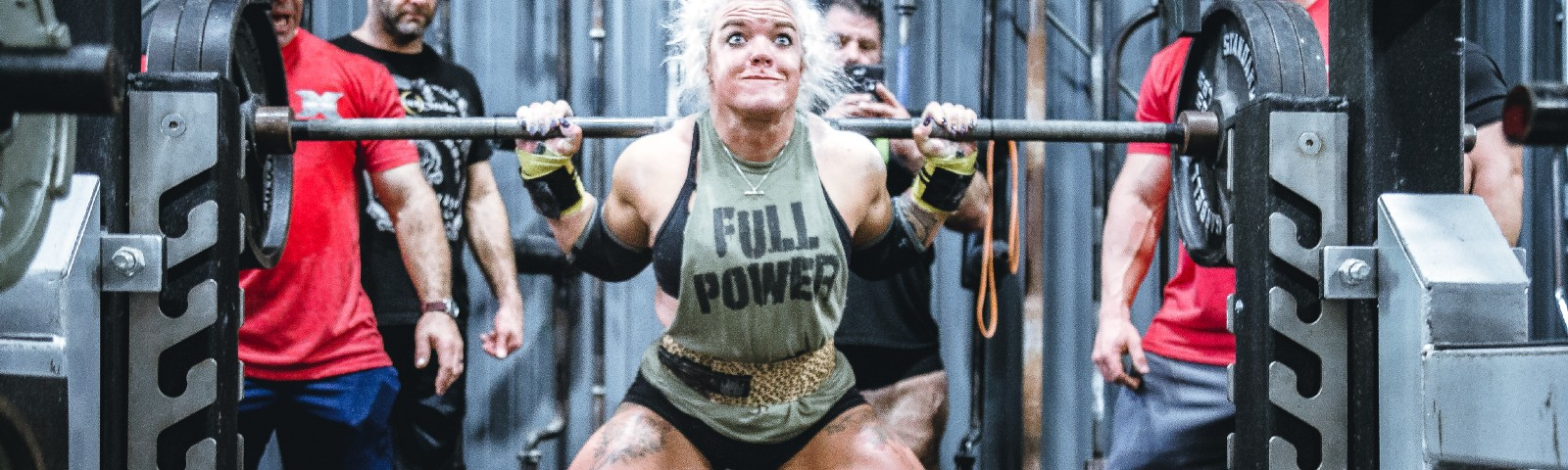 Woman lifting a very heavy barbell and grimacing
