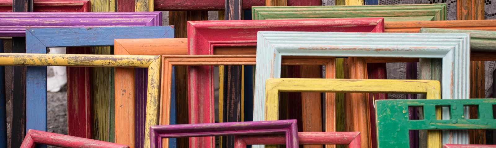 all sizes, shapes and colors of old wooden frames stacked against a wall and each other