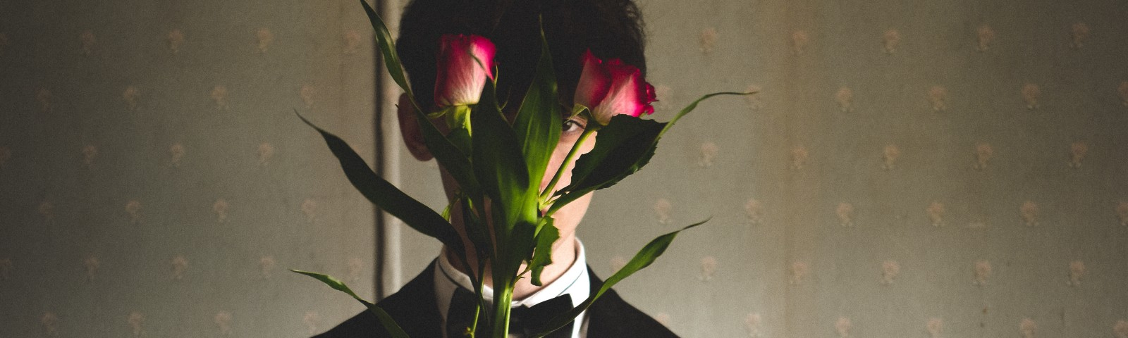 A man in a suit stands holding flowers up to his face.