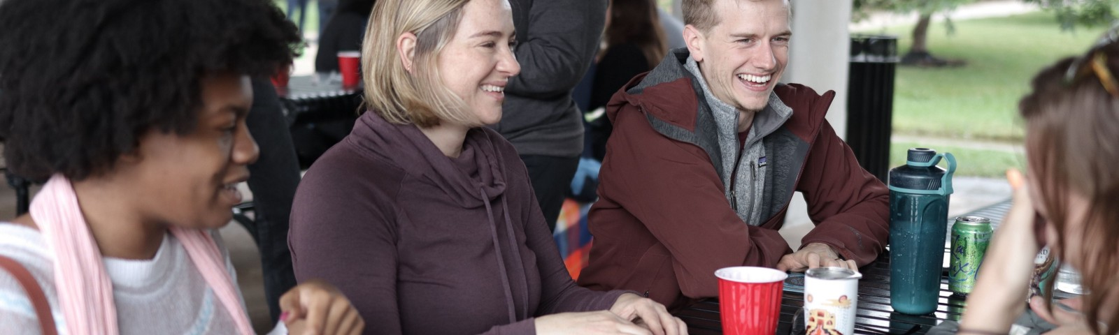 Three people site at a metal picnic table. There are cards on the table and they are smiling about to play a game.