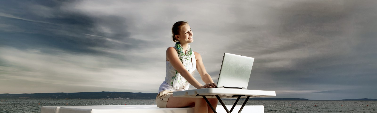 A girl on a waterside deck sending a thank you email after her interview to secure the job.