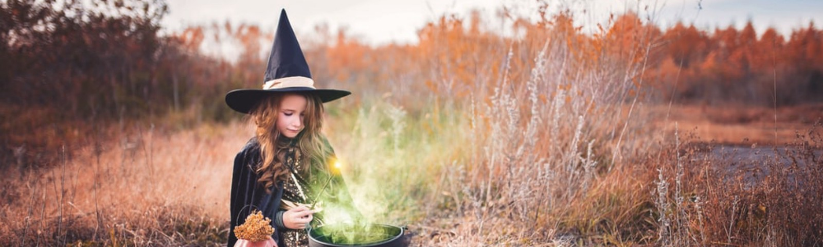 A young girl in a witch costume, in a field, accompanied by a pumpkin, tends a cauldron made from an old flowerpot.