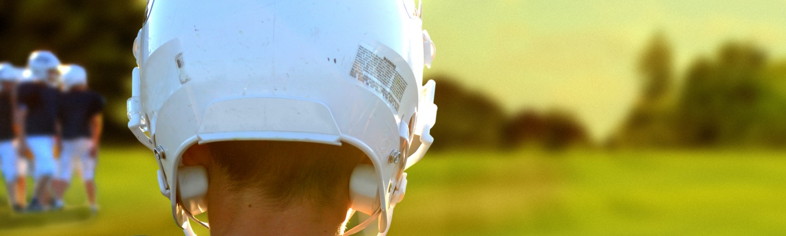 Back of a boy wearing a football helmet. He's looking out at football field.