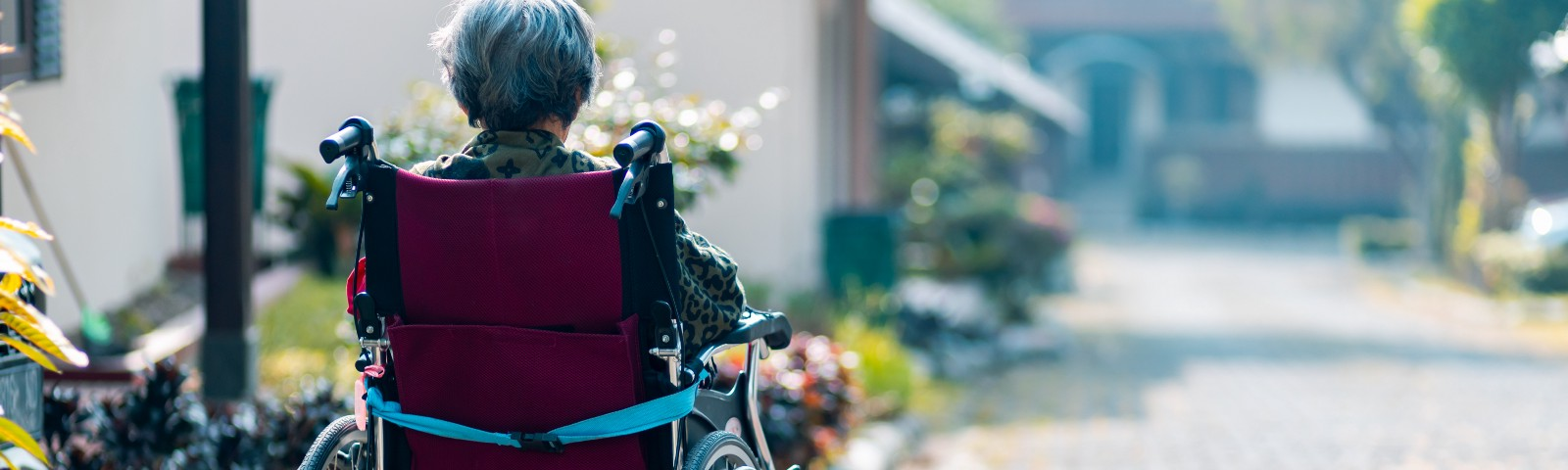 Older female adult in a wheelchair sitting outside all alone.