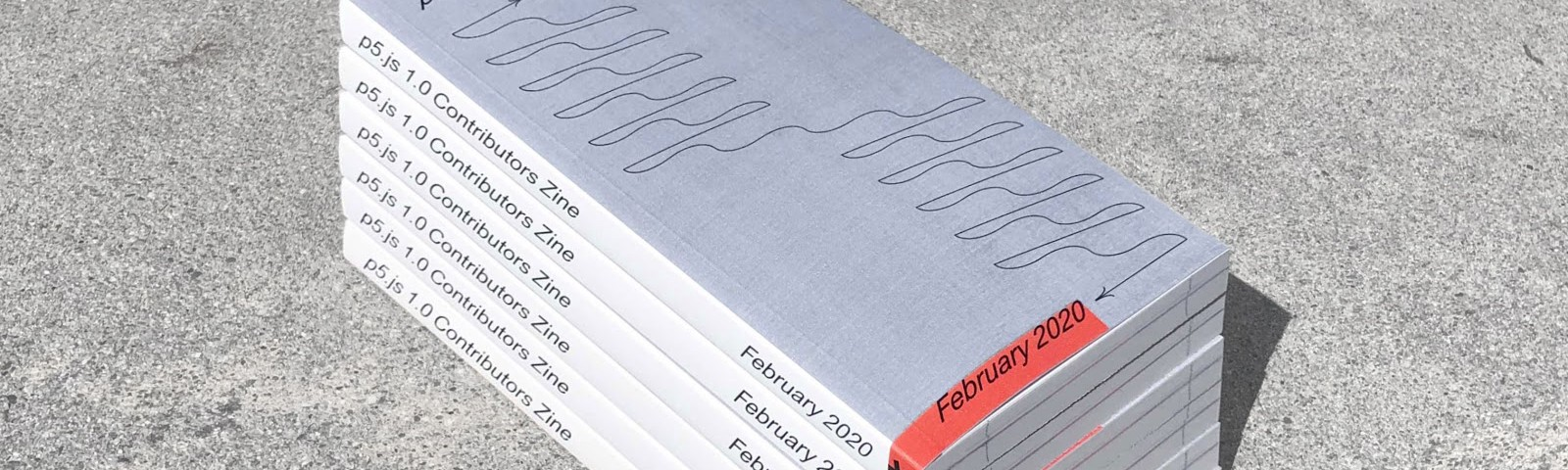 Six p5.js 1.0 contributors zines stacked on top of eachother on concrete.