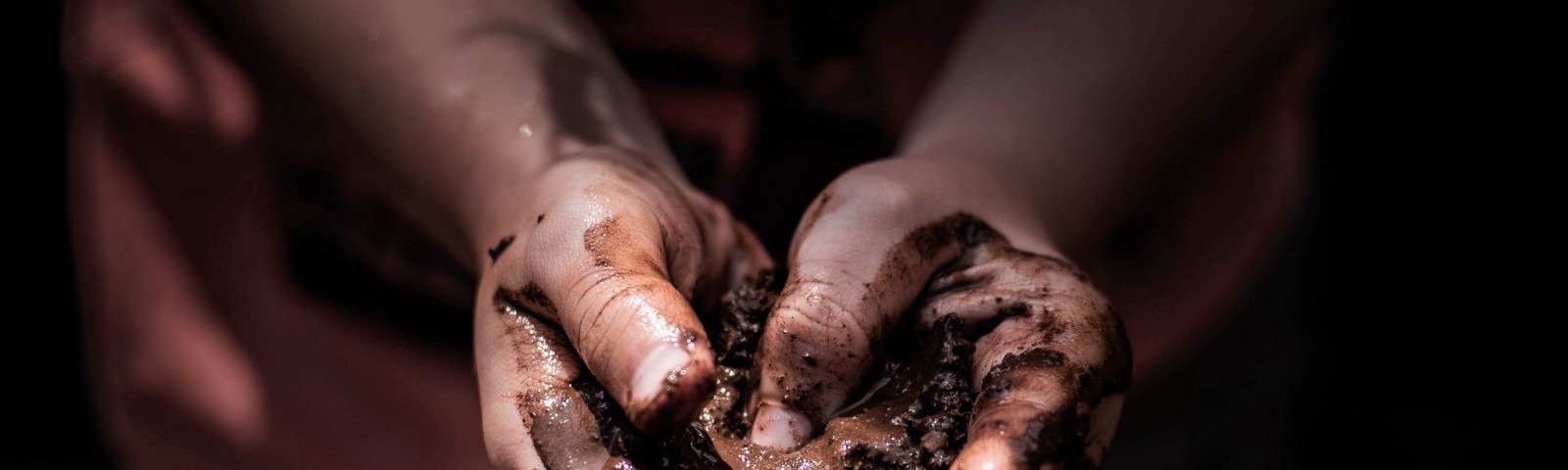 close up of child's hand holding mud and making heart shape