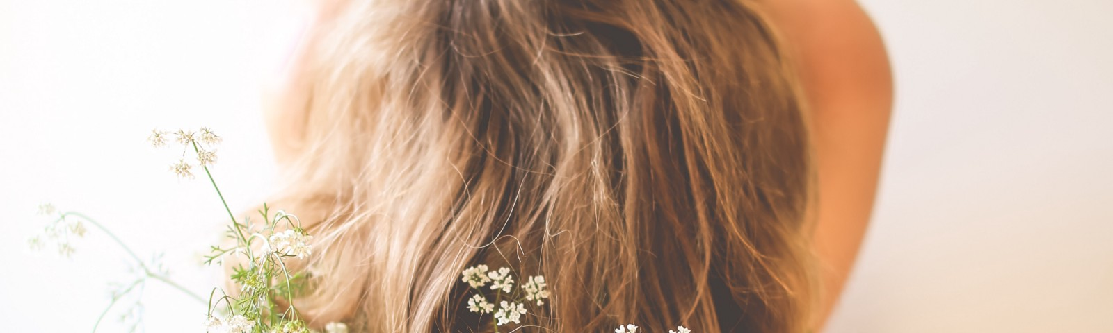 Naked blonde woman covered behind her long hair and a bouquet of greeneries with delicate white flowers.