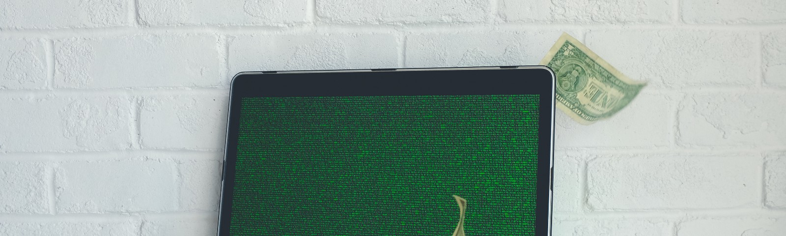 A few dollar bills floating around a laptop with a screen covered in green code.