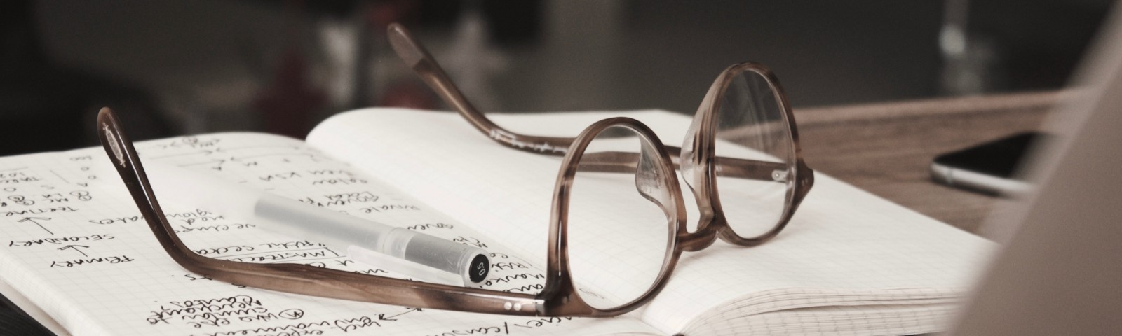 A pair of glasses and a black pen rests on an scribbled open notebook