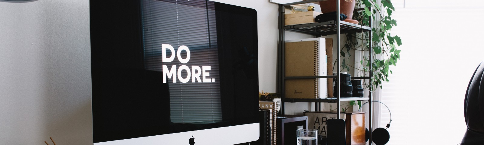 "A large screen on a desk reads ""Do More"""