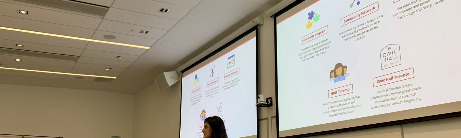 Sabrina Dominguez and Meha Shah  in front of a slide deck showing Code for Canada's various programs.