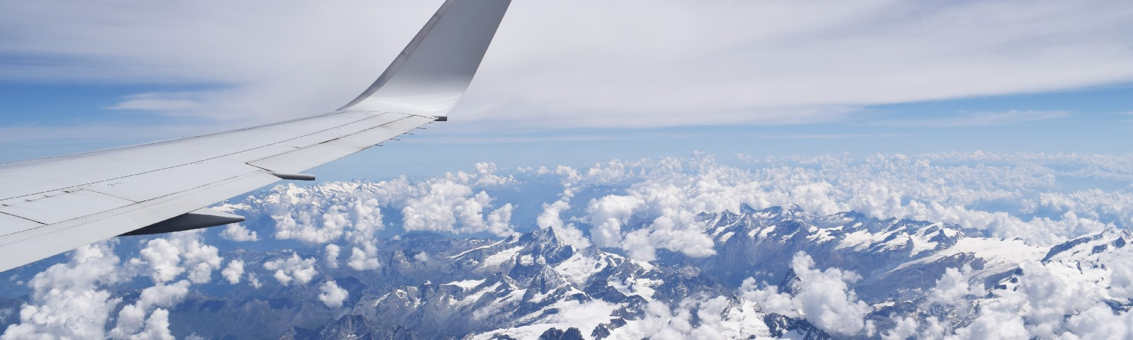 Airplane wing above clouds and mountains