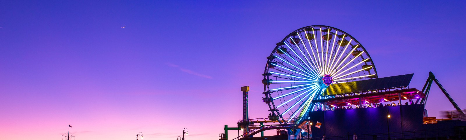 A Ferris wheel in an amusement park during the early evening
