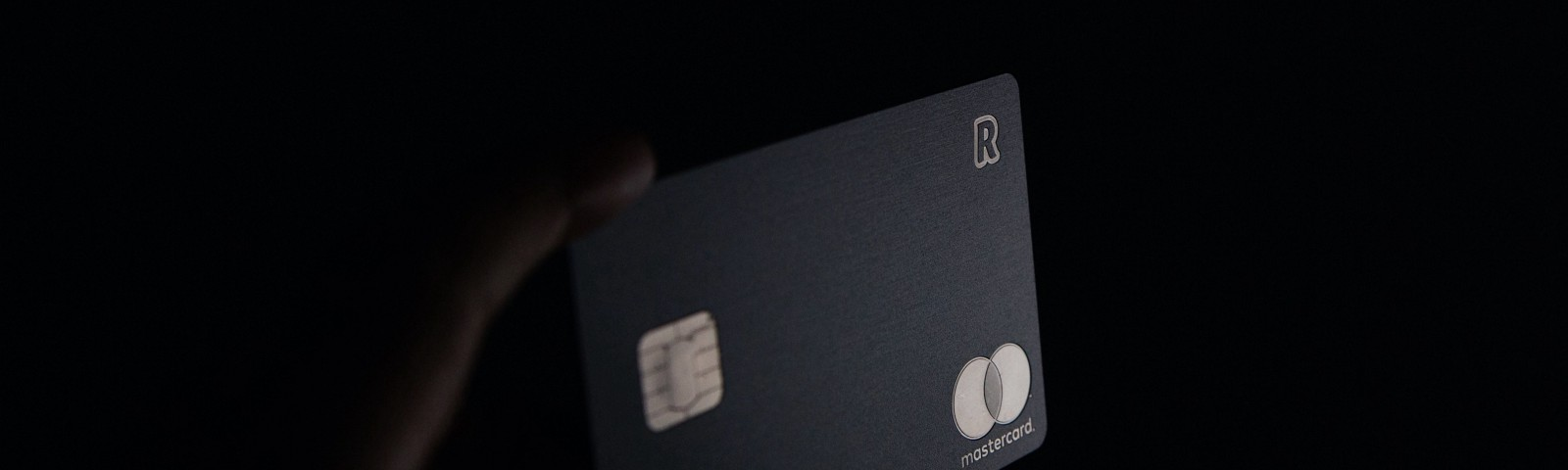 A hand holds a credit card up against a black background.
