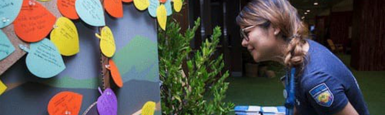 A Dreamforce employee peers over a desk to read text written on commitment leaves pinned to a tree.
