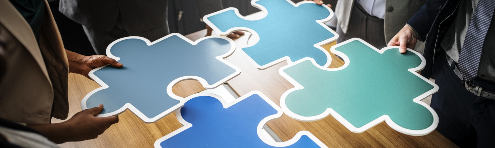 Four people, each holding a puzzle piece working together to solve the puzzle.