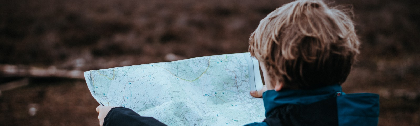 child standing in a field looking at a map