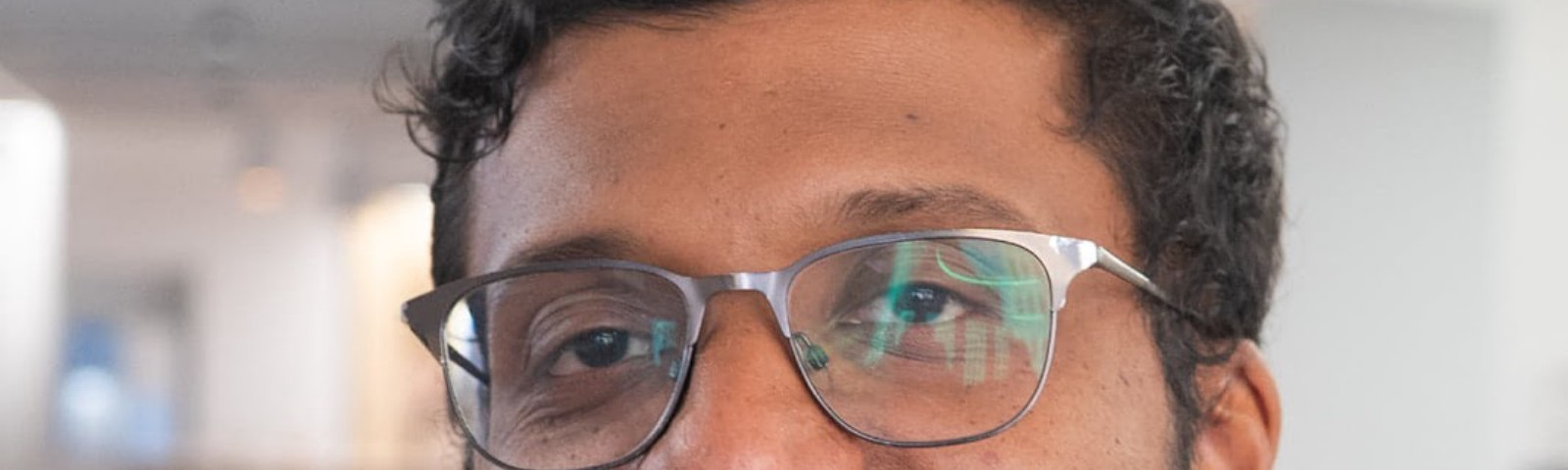 Person wearing a gray shirt and steel-framed glasses smiling at the camera. Out of focus background that looks like an office
