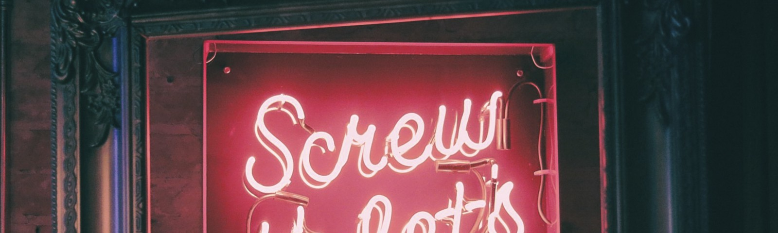 "Neon sign with the words ""Screw it, let's do it"" emblazoned in red."