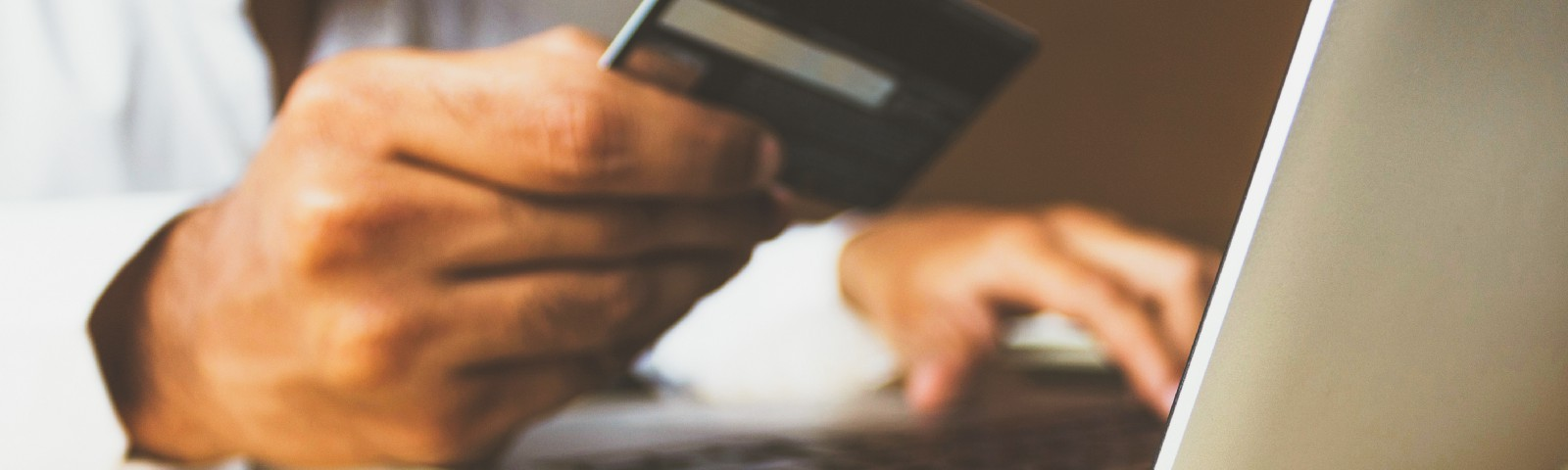 man making purchase on laptop with credit card