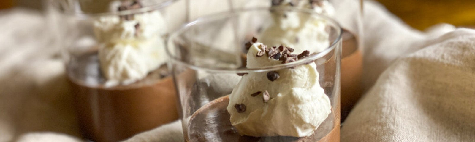 Three servings of chocolate mousse, served in glass tumblers, topped with whipped cream and cacao nibs