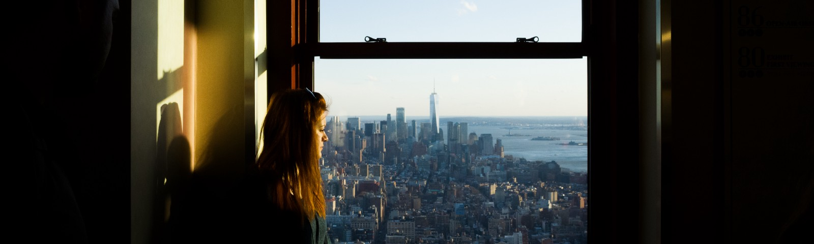 Woman looking out of window onto cityscape