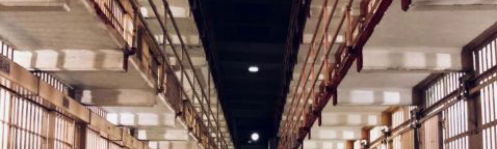 Photo of prison corridors, long stretch of cells.