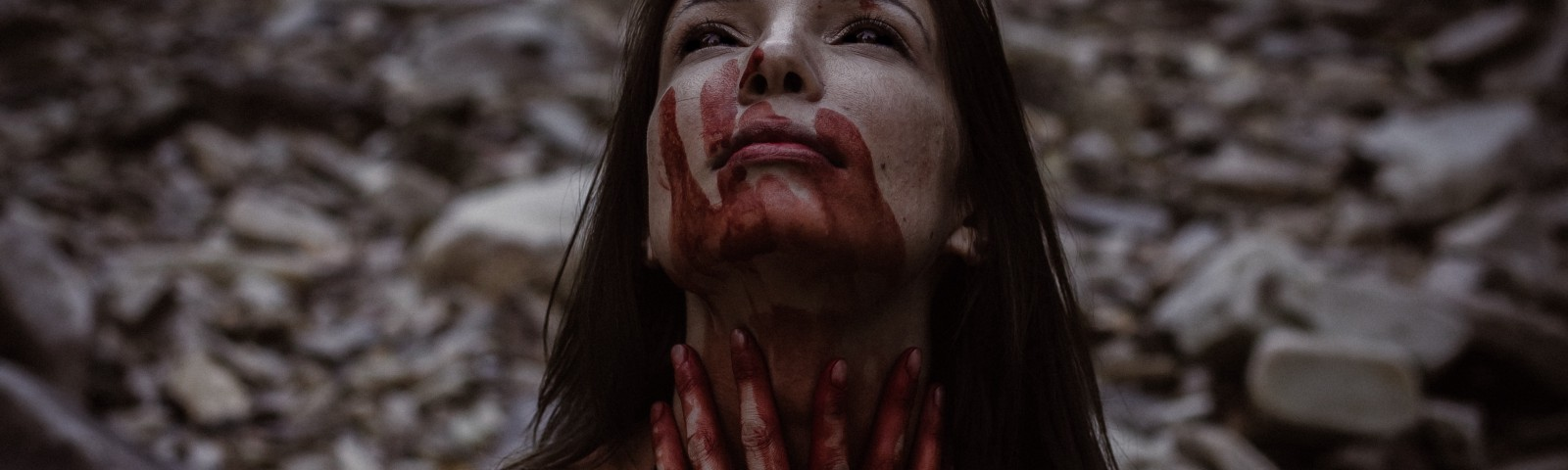 A lady covered in blood staring up into the sky. The blood may be from her hands.