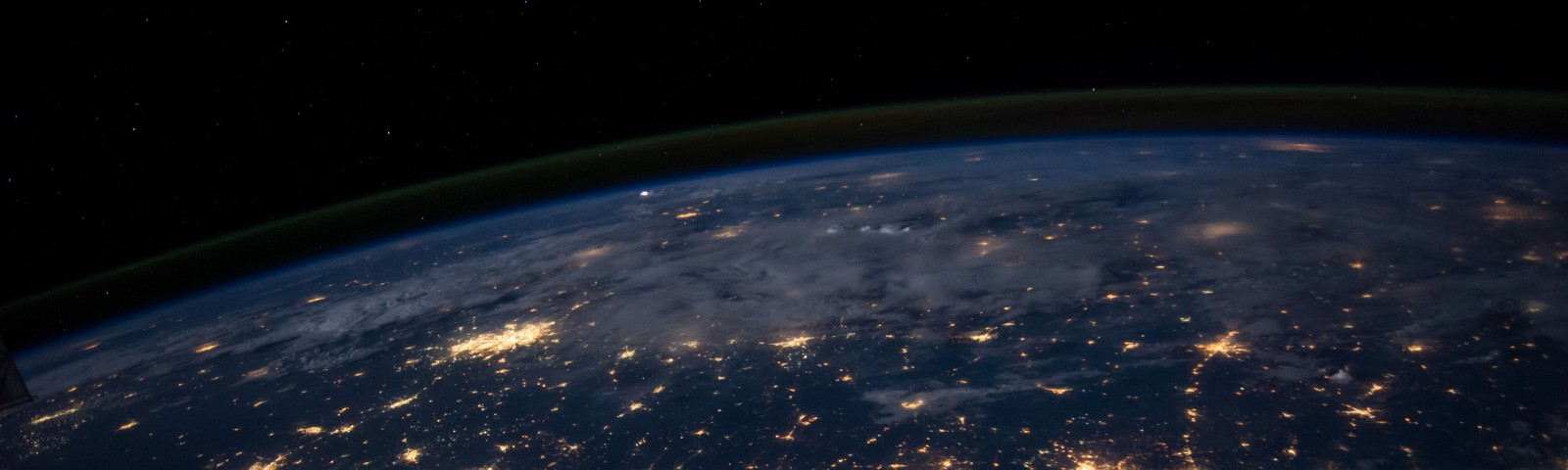 a picture of the Earth from space at night showing the glowing lights of cities