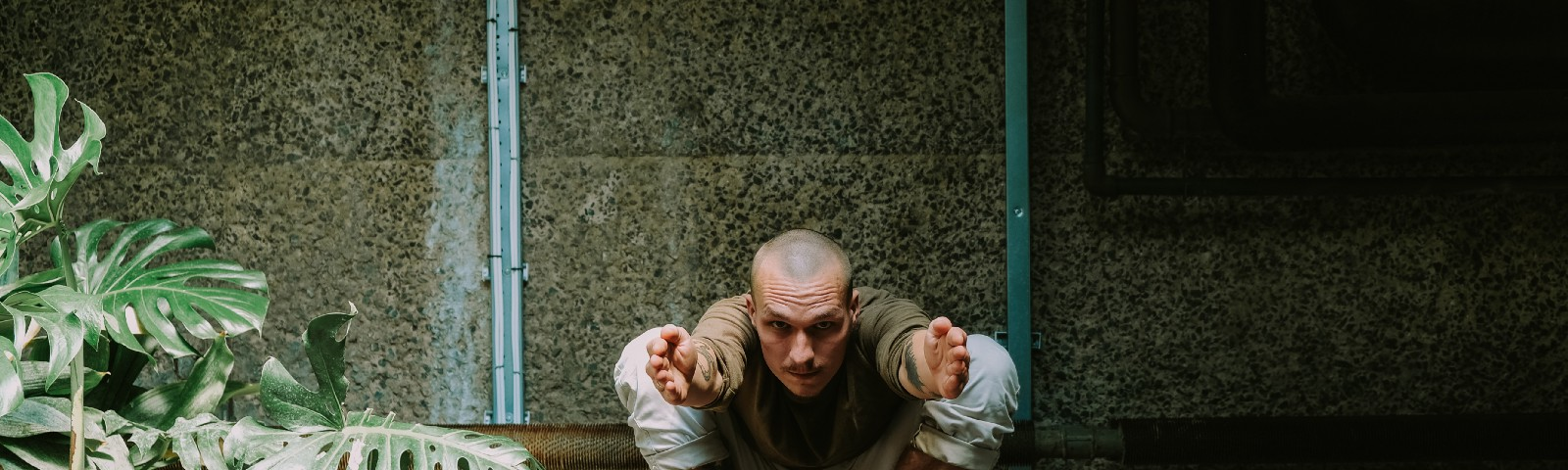 Man squatting in an advanced yoga pose, confronting the camera