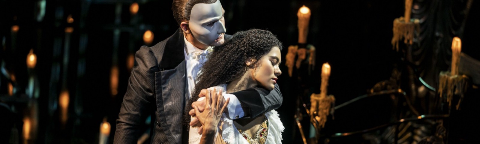 The Phantom (a dark haired white man in a suit with a white mask covering half of his face) holds Christine (a curly haired black woman in a white dressing gown) on a candlelit set.