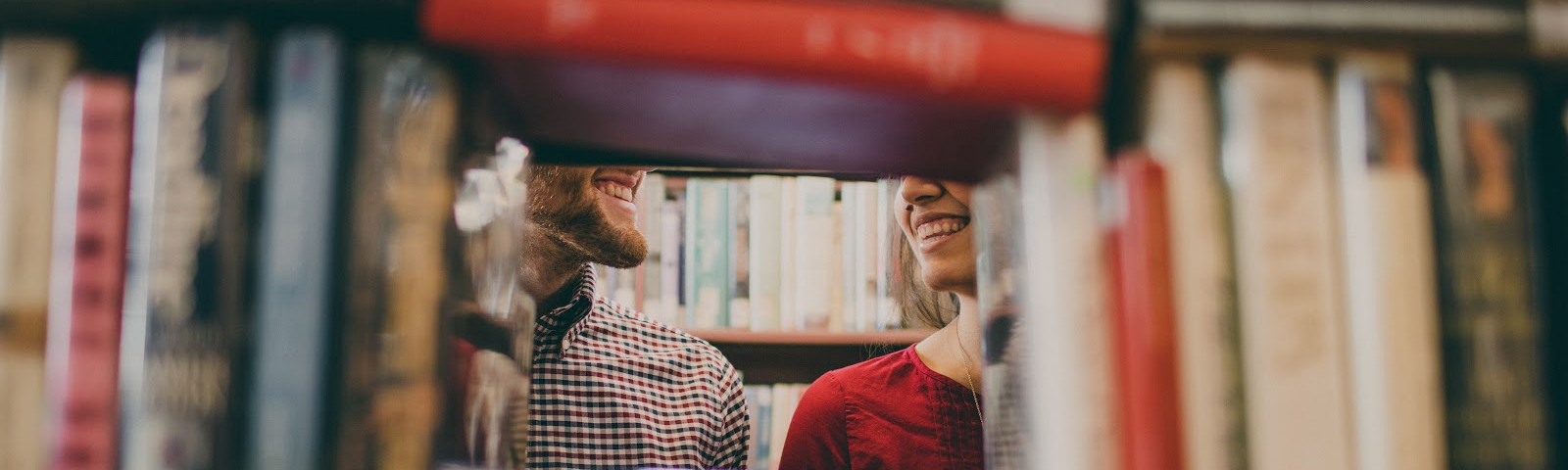 Image of couple smiling framed through a hidden hole in a bookshelf.