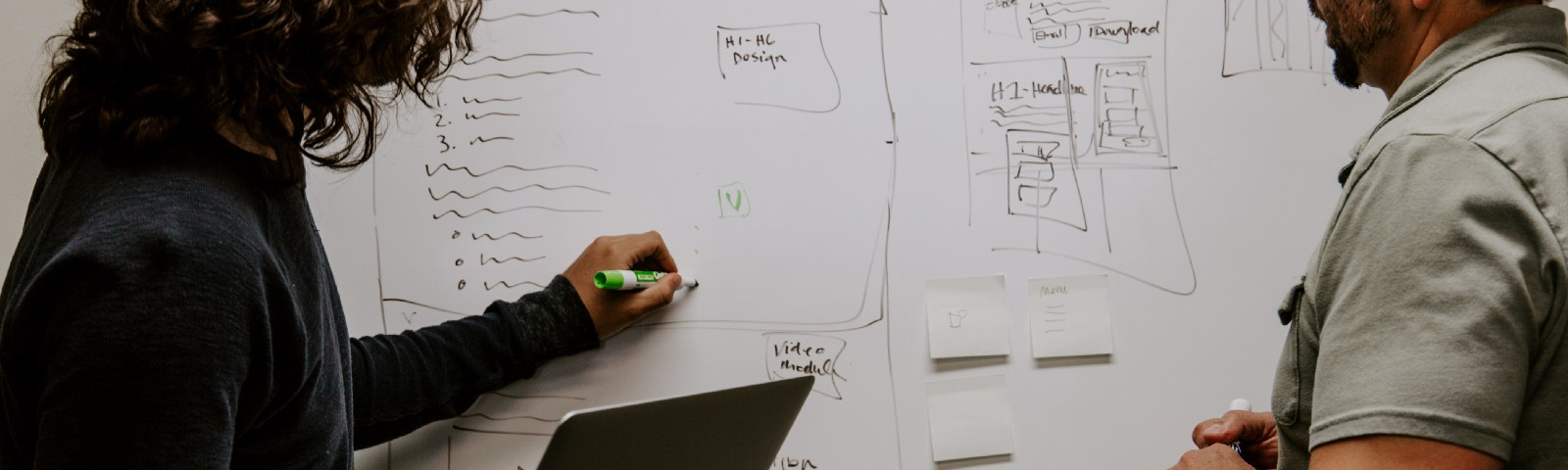 Two designers collaborating using a whiteboard