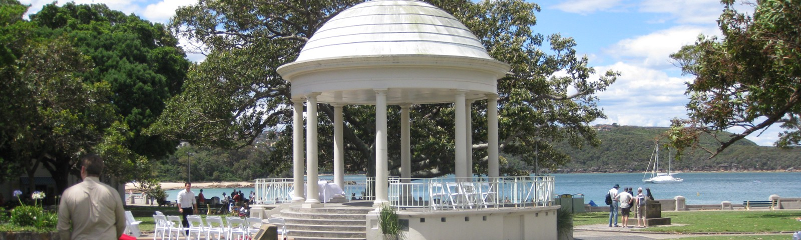 A large, raised rotunda with a white, dome shaped roof, in a grassy waterside park with a boat moored in the distance.