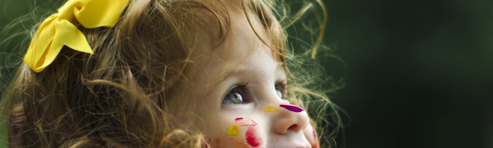 Little girl with a big smile, looking up and photographed from her right side. Brown hair and green eyes, with a yellow bow in her hair and lots of colorful paint stains on her nose, cheeks, neck, and white blouse.