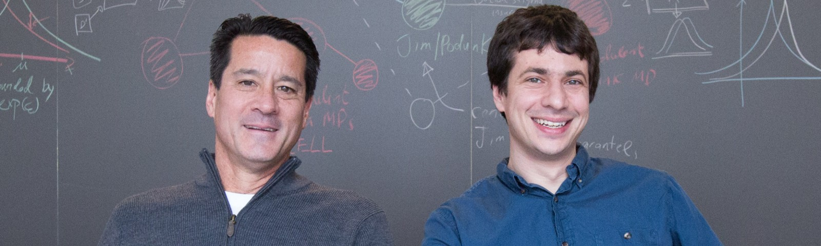 Michael Kearns and Aaron Roth sit in front of a chalkboard.