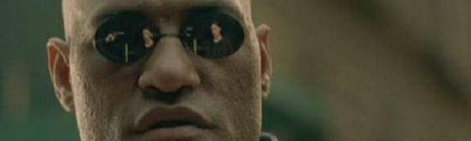 Morpheus from the Matrix staring into the camera with black sunglasses on
