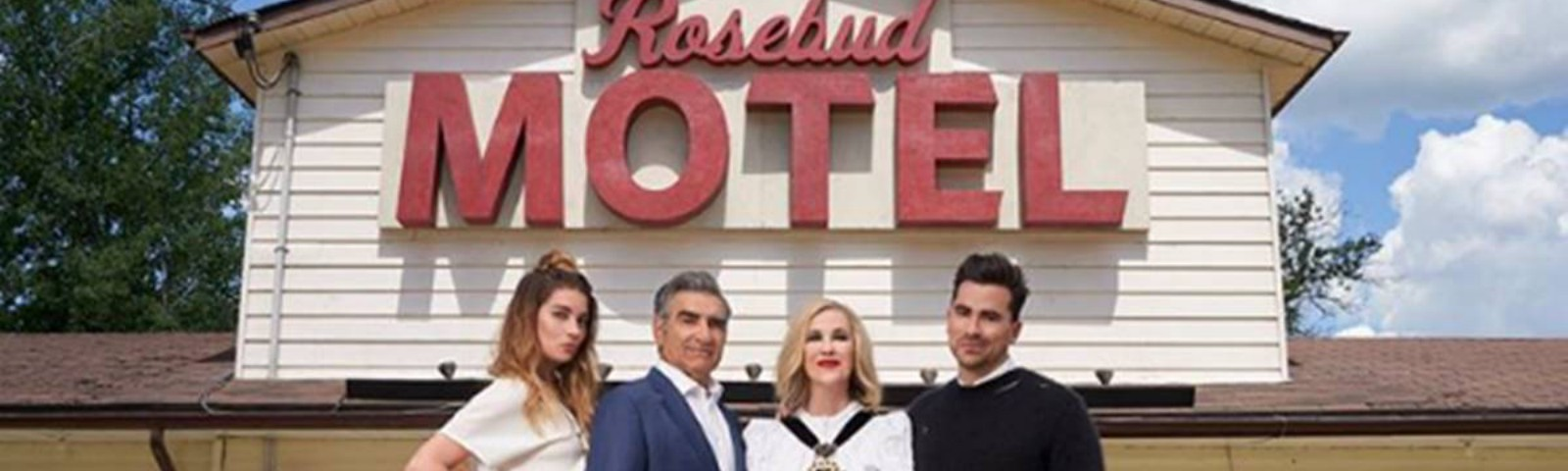 The Rose family (Alexis, Johnny, Moira, David) pose in front of their new home in Schitt's Creek, the Rosebud Motel.