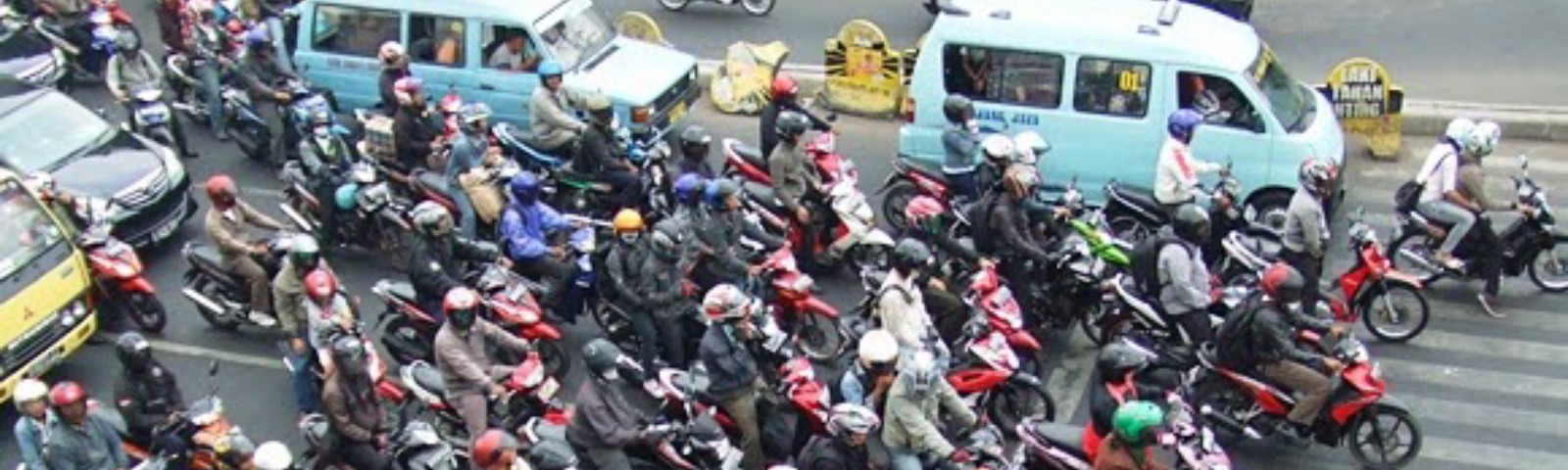 Many motorcycles and cars at a traffic intersection, without much regard for lanes. One rider is checking his phone.