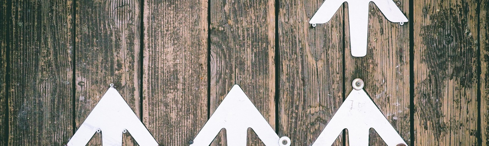 White arrows facing upward screwed to a rough wooden background