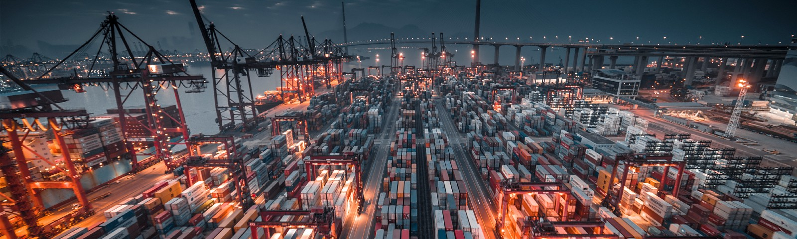 An image of a port with lots of shipping containers stacked up