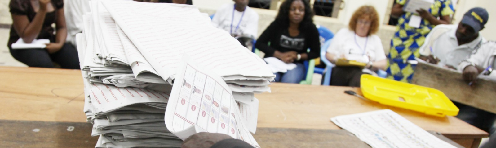 Person counting votes with observers watching in background