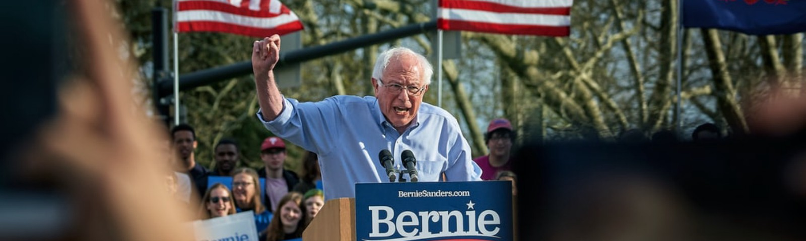 Bernie Sanders standing at a podium during a rally