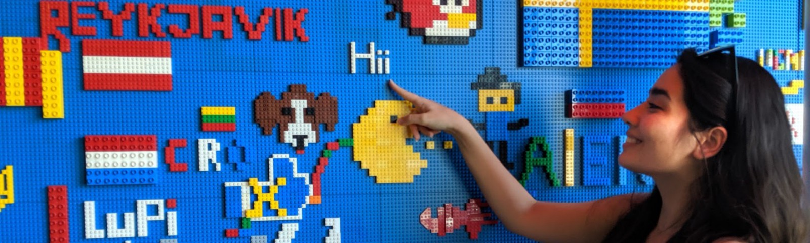 A person with long black hair smiles and points at a multi-colored wall made of legos.