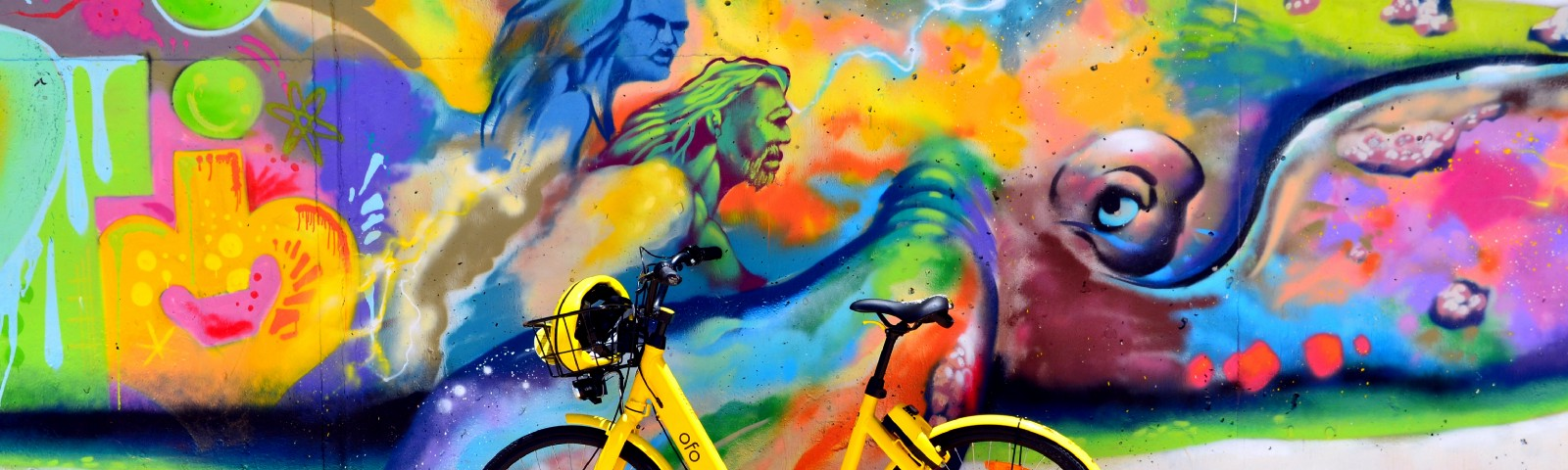 a yellow bike in front of an abstract mural