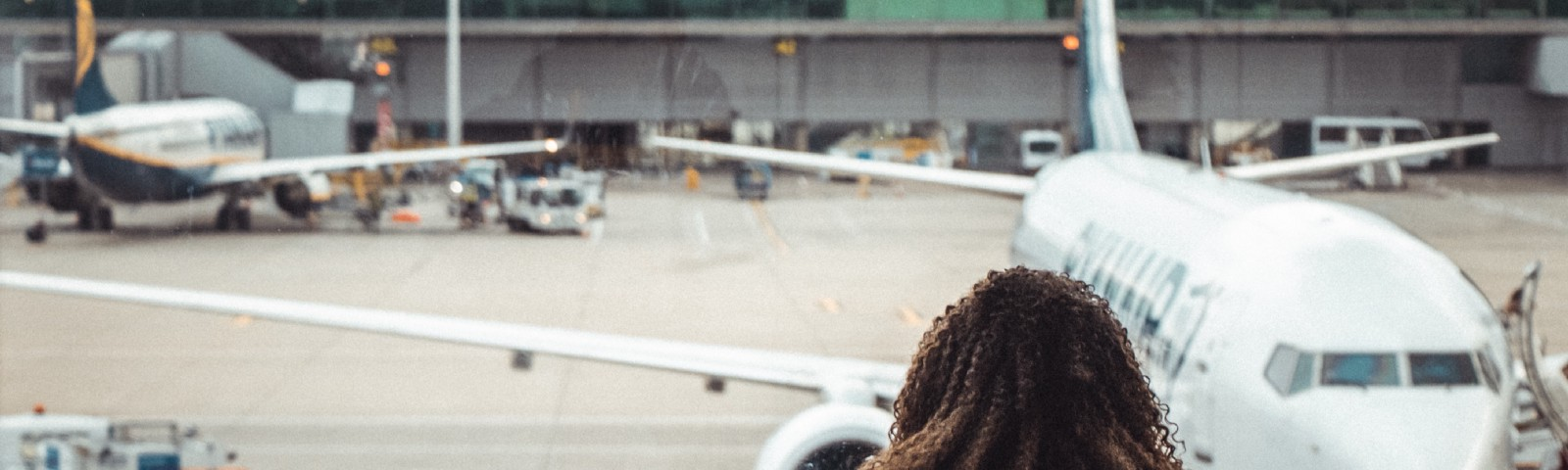 A woman stares out at a plane from a departure lounge at an airport