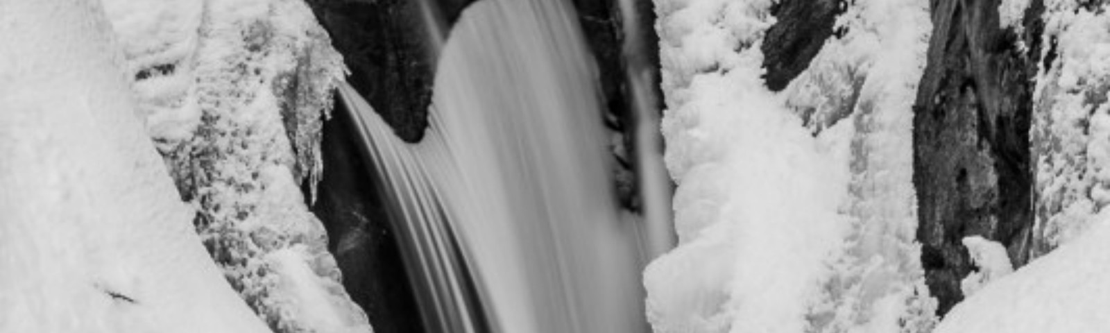 A black and white Pacific Northwest nature photograph of a snow covered, partially frozen Christine Falls at Mount Rainier National Park, Washington.